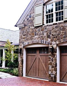 Stonework, wood carriage house garage doors, brick paver driveway and shutter paint color.