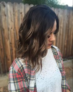 Caramel balayage highlights, dark brown root on short hair and a beach wave style