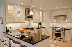 white kitchen peninsula with black ceramic countertop and double chrome pedant lighting