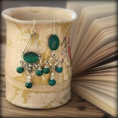 Behold the enticing blend of these green Chrysocolla stones combined with silver, surrounded by mischievously playful shapes, creating a truly enchanting pair.
