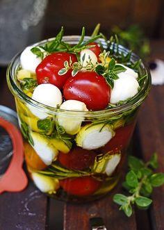 Cocktail-Tomaten mit Mozzarella-Kugeln eingelegt in frische Kräuter und Olivenöl