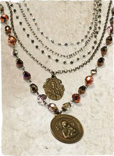 The multi-stranded chain and bead necklace is adorned with cast replicas of antique French medallions.