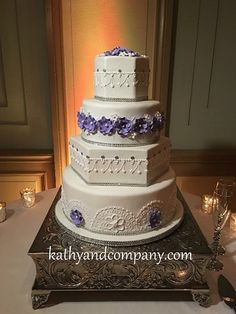 Intricately piped wedding cake with purple sugar flowers and sliver glitter details.