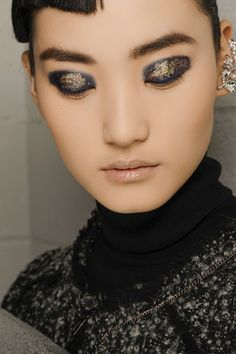 Golden glitter was applied over the top to create a dramatic eye look - complemented by pale, glossy lips and flawless skin.