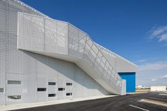 HDE 17 I Poggi architecture + MORE Architecture I La Rochelle, France I The outside skin is made of white expanded steel panels wrapped around the building. It gives the building a clean and high-level process look. The main entrance and trucks access way are landmarked by a striking canopy covering a blue void.n