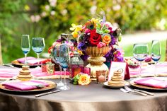 so colorful + love the peacock feathers in the centerpiece. and blue glasses. and magenta napkins. yeah, I love this.