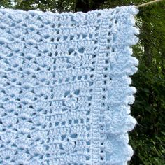 Listing is for a Pale Blue baby blanket made from a marle yarn ... white thread twisted around a blue yarn ... crocheted in a pretty shell pattern framed in squares of rosebuds. -- 36 x 27 Care is easy, just machine wash on gentle and tumble dry on low heat. This item has been