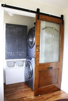 Sliding door flat track barn door for the laundry room. I especially love the reused vintage office door!