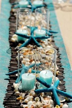 Beach-Inspired Table Decor - shells and collected driftwood, blue candles and table runner add a seaside theme to the centrepiece. | The Micro Gardener