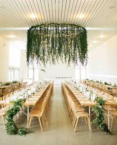 Spring Wedding Ideas from Real Celebrations   Martha Stewart Weddings - This couple proved that you don't need to add a single flower to create spring vibes at your wedding reception. Their major greenery chandelier stole the show. #weddingflowers #springweddingideas
