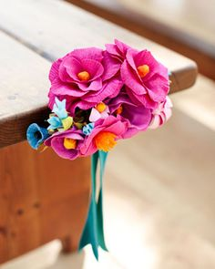 For this outdoor ceremony, the pews were decorated with vibrant crepe-paper bouquets