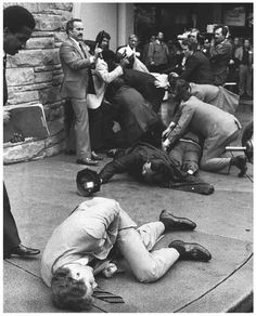 Secret Service agent, Tim McCarthy clasps his stomach after being shot spreadeagling himself between Ronald Reagan and John Hinckley Jr. March 30, 1981