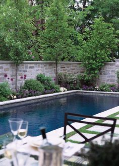 With this substantial stone wall and careful choice of plants, the pool can be close to the edge of the yard and still feel secluded.