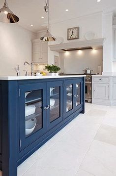 Amazing blue kitchen design with metallic pendant light, white walls and white floor tile