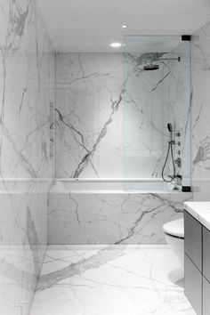 In another bathroom, the Carrara marble remains in slab form.  Photography by Adrian Gaut.