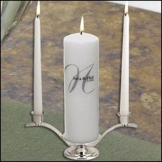 """Unity Candle Set - Elegance - White - WeddingDepot.com - 010-PC1255SW-NI Romance will be the theme of your big day with this gorgeous Elegance Unity Candle. With its one of a kind personalization and classic form, this unity candle will remain a treasured keepsake for years to come.    Three piece set includes a pillar unity candle, two tapers and a silver  candle stand.  Pillar candle measures 3"""" by 9"""". Tapers measure 10"""". Gold stand measures 4 1/2"""" wide by 12 1/2"""" long by 4 inches tall."""