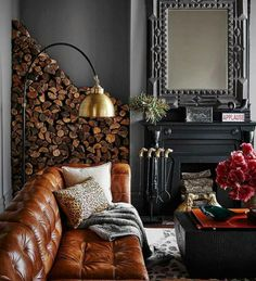 Life by the fireside is just cozy in a living room like this! The dark iron fireplace w/ the wall of logs is very homey. Especially love that gold lamp & the mirror!