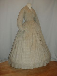 """1860s gray & white cotton dress with sprig pattern, self fabric ruffles on neck, front opening & sleeve cuffs, piping on armscyes; bodice lined in cotton, lining has hook & eye closure, cotton print has black button closure, cartridge pleated skirt, skirt unlined; bust: 36""""; waist: 30; skirt length: 40; hem width: 124"""""""