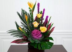Tropical funeral arrangement of birds of paradise, roses, purple liatris with beautiful tropical foliage and trendy purple cabbage leaves. Suitable design for t