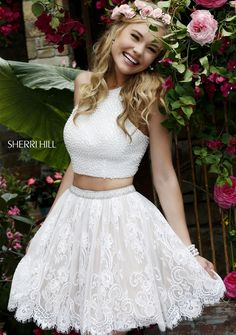 Showcase shimmering sweetness in the Sherri Hill 32313 two-piece short prom dress. The halter neck crop top is exquisitely embellished with all over pearl beading. The A-line lace skirt features a pearl beaded waistband and flares in softly gathered layers into a mid-thigh scalloped hemline with eyelash trim.