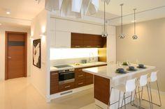 Zabudowę kuchenną umieszczono tylko przy jednej ścianie. Dzięki temu aneks kuchenny stał się subtelnym tłem dla aranżacji całej strefy dziennej.