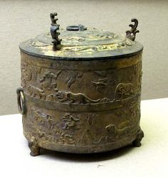Wine-Warming Vessel, Western Han Dynasty, 26 BC, Shanxi Museum.  The vessel is decorated with animals and birds in shallow raised relief, upon a blank background.