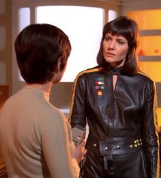 Scary lesbian approaches the innocent and amenable Sandra. Of course she needs to be wearing leather. I want her haircut.