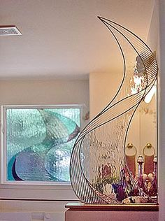 Glass sculptural piece that divided the vanity from the entry way.  It also ties into the leaded glass window piece in the background.