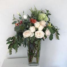 Flower arrangement with roses, pokeberry, hydrangea, eucalyptus, lisianthus, alstroemerias