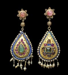Two Qajar gem-set gold Earrings. Persia, 19th Century. Each of drop-shaped form, with gem-stones in raised gold settings, surrounded by a narrow blue enamelled border and a seed pearl edge, with seed pearl suspensions on twisted gold wire, verso with polychrome floral enamelled decoration, surmounted by gem-set floral and globular gilded silver filigree elements probably added later, with screw and loop. Image: Bonhams