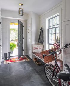 Gray and white cottage mudroom boasts a glass paneled gray door framed by a white wall accented with white panels and opening to a red and blue rug placed on gray slate floor tiles.