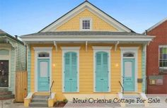 New Orleans Cottage For Sale is bright yellow with turquoise shutters and door. Historic cottage with exposed brick fireplaces and plenty of modern updates.