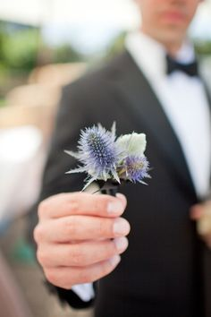 love this, groom holding out bout before putting on. It's like typical bouquet shot for the bride....