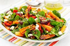 Roasted beets and carrots look beautiful and taste even better in this easy-to-make spinach salad. Top with dressing and feta for the win.