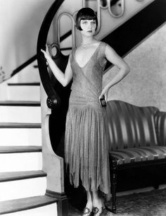 Louise Brooks c. 1925: Louise Brooks standing by the stairway