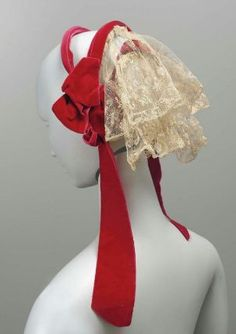 1860s: Woman's cap made of three wire bands covered with bright red velvet ribbon; two deep ruffles of machine-made lace sewn to bands across back; velvet ribbon bows and ties at sides
