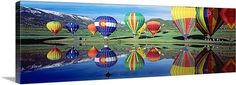 Reflection of hot air balloons on water, Colorado Wall Art. Vividly colored vehicles for the aeronautical sport gather around a lake and reflecting in the water.