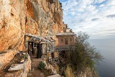 The holy mountain: monks of Mount Athos – photo essay | Art and design | The Guardian; Monks look out from their cell which clings to the cliffs of Karoulia