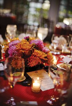 "Pink and Orange Dahlia Centerpiece. As for the centerpieces, ""I wanted to keep the design low and simple,"" Stacy says. ""Just a mix of dahlias in a vase with black pond rocks around it."""