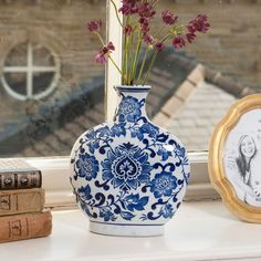 """This vintage style ceramic vase is the perfect decorative accessory for any room in the home, featuring a white and blue floral design and a narrow base.   Place on a mantel piece, on a windowsill or at a table setting for a classic touch, perhaps holding a stem of fresh flowers. This elegant and timeless piece would suit both modern and classically styled interiors.   A great gift idea for someone who likes antique style collectables!"""""""