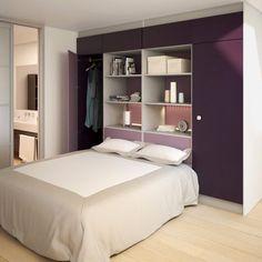 Pour optimiser l'espace, la tête de lit comprend une armoire et des espaces de rangement, et la séparation avec la salle de bains se fait par une porte coulissante.