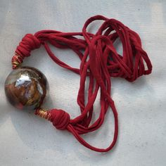 Necklace made of ceramic. It has a sphere in it, empty inside  so very light; it is decorated with pieces of crystal and red metal, encircle with a red ribbon. This artwork was handmade in Italy by Giraerigira.