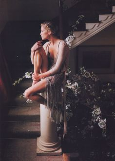 girl sits on pillar of marble stair well in ethereal nude dress with many flowers