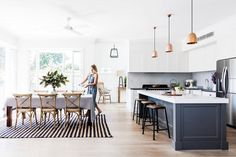 A modern open-floor plan kitchen with a gray island, bronze pendant lights and wood floors