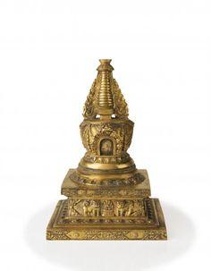 Tibet Epoque XVIIIème siècle - Stupa reliquaire en bronze doré, le corps principal à décor de pendeloques, reposant sur une base carrée ornée de lions bouddhiques et joyaux sacrés parmi des motifs stylisés, la partie supérieure formée d'une superposition de parasols, la base fermée gravée d'un visvavajra H : 15 cm Tibetan Art, Tibetan Buddhism, Buddhist Art, Art Asiatique, Parasols, Bronze, Objet D'art, Ropes, Decoration