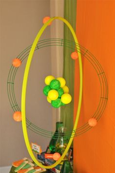 Science party decor: large scale atom using a hula-hoop, wire wreath, paint, and styrofoam balls. (Probably can find something besides styrofoam...)