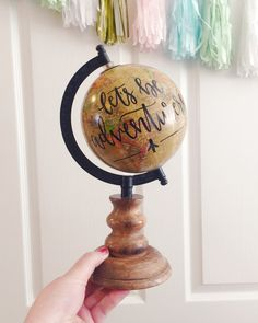 """A hand painted globe that reads """"let's be adventurers"""" in black paint. The aged yellow-colored globe stands about 10"""" tall with a wooden base."""