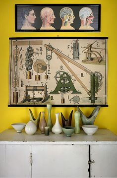 Midcentury pottery on a primitive cabinet with school wall charts.