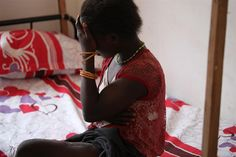 """Sudan, 2011: """"Grace"""" covers her face in a dormitory for children rescued from the Lord's Resistance Army (LRA), a Ugandan rebel group. She was abducted by the LRA two years ago. """"On the way, they separated the men and killed them,"""" Grace said. """"They said if we tried to escape they would kill us."""" She was rescued in southern Sudan (now South Sudan). With UNICEF support, Grace was reunited with her family. ©UNICEF/ Mia Farrow - http://www.unicef.org/photography"""