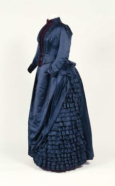 Two-piece afternoon dress of dark blue, partially pleated silk atlas, circa 1887, with trim of purple silk velvet, chenille, and bead appliqués. Whalebone stays, skirt with steel hoops, and cushions to support bustle.